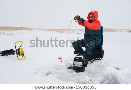 Ice fisherman reeling in a fish - stock photo