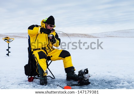 Ice fisherman with a fish on his line. - stock photo