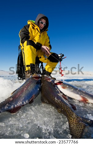 Ice fisherman with his catch of rainbow trout on the ice