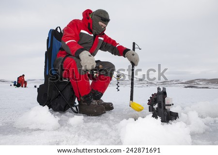 Ice fishermen fishing on a cold overcast day. - stock photo