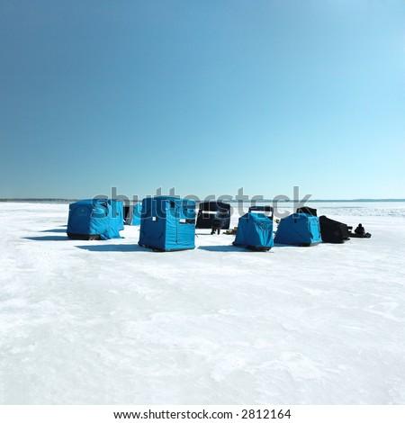 Ice fishing camp on a large lake - stock photo