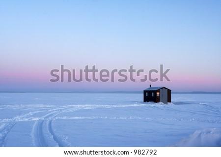 Ice fishing hut on a frozen lake during sunrise. - stock photo