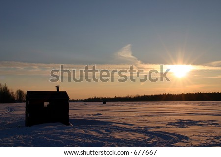 Ice fishing hut on a frozen river - stock photo