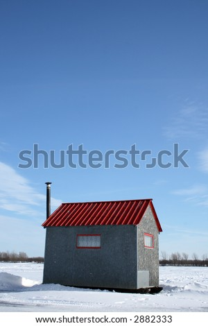 Ice fishing hut with red roof and chimney under the blue sky. - stock photo