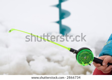 Ice fishing scene: typical rod with line, drill. - stock photo