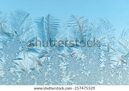 Ice floral pattern on glass in blurred vignette. Macro view. Holiday seasonal background - stock photo