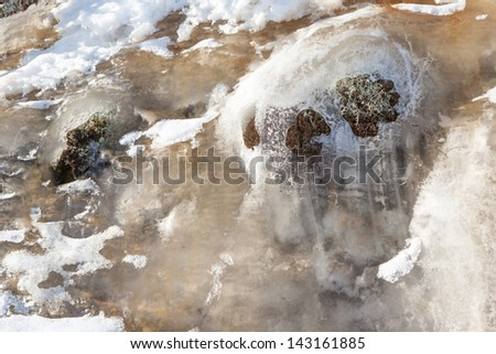 Ice flowing down on a stone on the bank of winter lake the Natural background