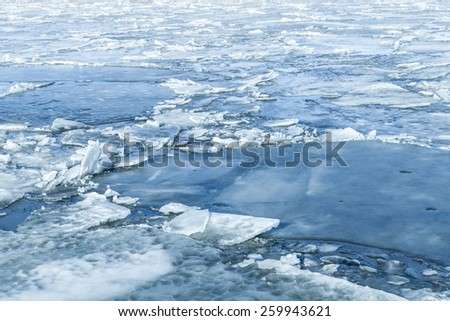 Ice fragments covered with show on frozen river water. Dark blue natural background - stock photo