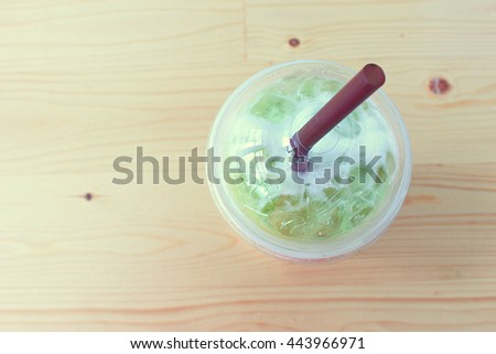 Ice green tea on the wooden background from the top view shot selectuve focus on the lid of the glass - stock photo