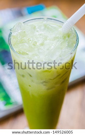Ice green tea on wood table - stock photo