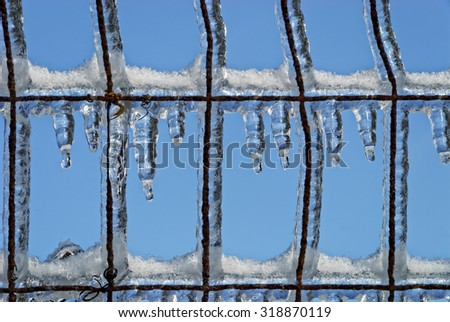 Ice Hanging From Wire Fence Against Blue - stock photo
