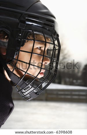 Ice hockey player boy in uniform and cage helmet concentrating. - stock photo