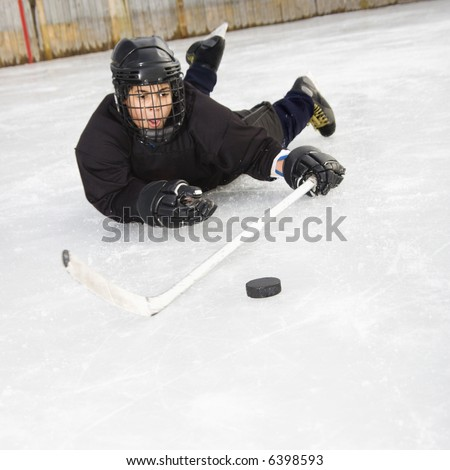 Ice hockey player boy in uniform sliding on ice holding stick out towards puck. - stock photo
