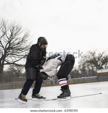 Ice hockey player boy roughing up another player on the ice rink. - stock photo