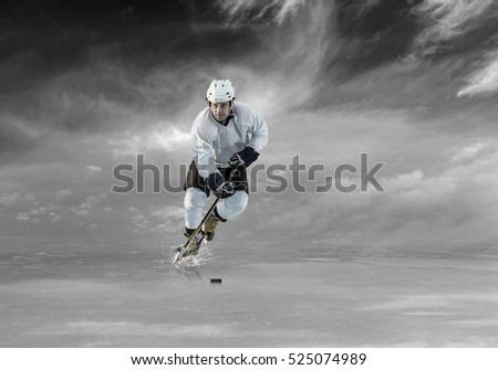 Ice hockey player in action on the ice outdoor under sky.