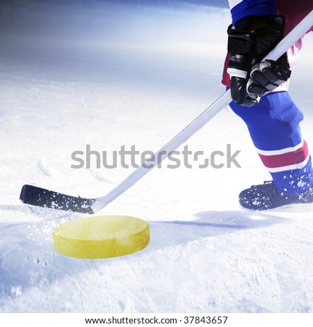 ice hockey player shoots golden puck - stock photo