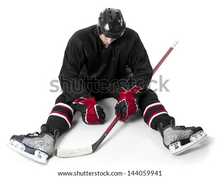 Ice hockey player sitting on ice with disappointment - stock photo