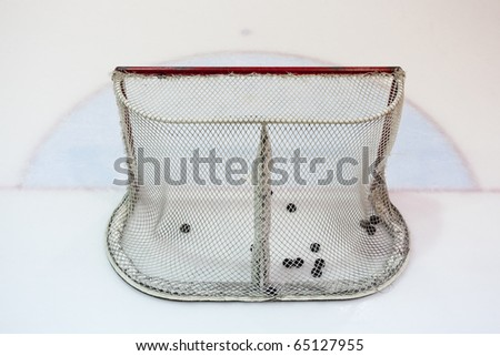 Ice hokey net filled with pucks, seen from behind. - stock photo