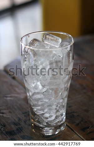 ice in a glass isolated on wood table. - stock photo