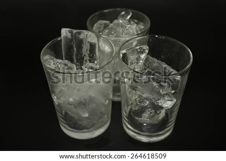 Ice in a glass on a black background.