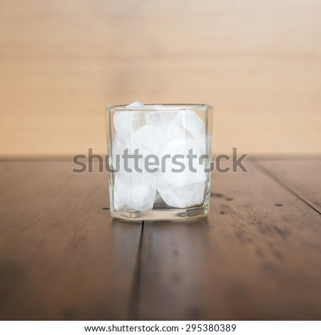 ice in glass of water on wood background - stock photo