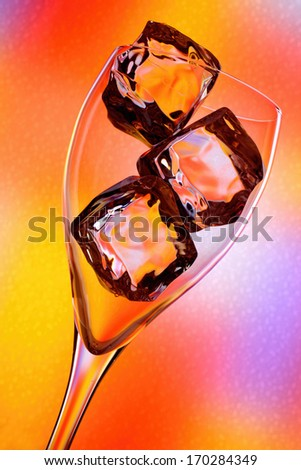 Ice in glass with many colored background. - stock photo