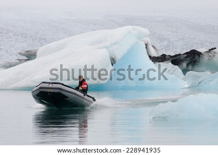 ICE LAGOON, ICELAND - Sept 5 2010: Man in motor boat - Jokulsarlon lagoon, glacier lake, Iceland.  Sept 5 2010. Ice Lagoonis one of the famous attraction with lot s of tourist in the southern Iceland - stock photo