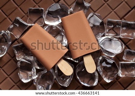 Ice lollies on ice cubes and bar of chocolate