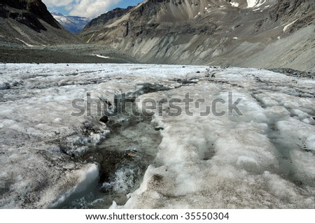ice melting on a glacier causes a river on its surface. Global warming is causing the worlds glaciers to melt - stock photo