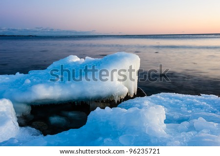Ice melting on the beach in the sunset with open water in the background - stock photo
