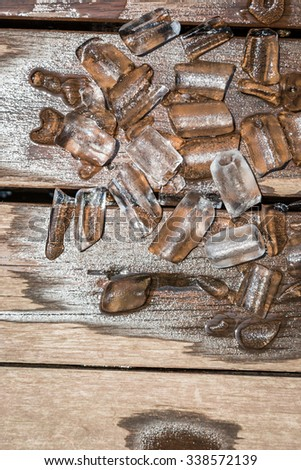 Ice melting on the wooden floor background - stock photo