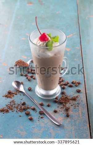 Ice Mocha / Chocolate Coffee drinks with whipped cream, red cherry and mint on top, on rustic blue background - stock photo