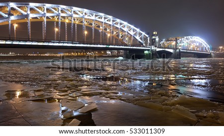 Ice near old city metal arch bridge across the Neva River in early winter, Bolsheokhtinsky Bridge (or Peter the Great Bridge), Saint Petersburg, Russia
