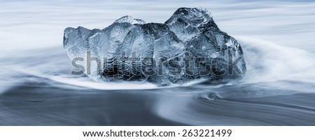 Ice on ice beach with water wave in Jokulsarlon, Iceland - stock photo