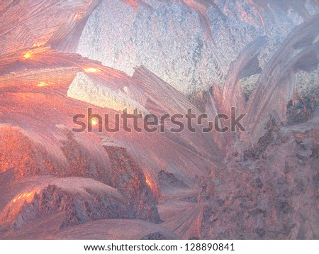 Ice patterns and sunlight on winter glass - stock photo