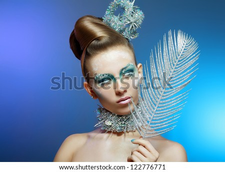 Ice-queen. Young woman in creative image with silver blue artistic make-up and perfect hairstyle. - stock photo