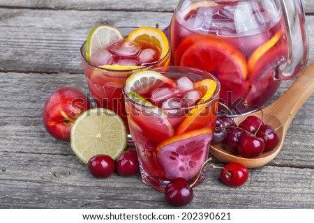 Ice refreshing summer drink with lots of different fruits - stock photo