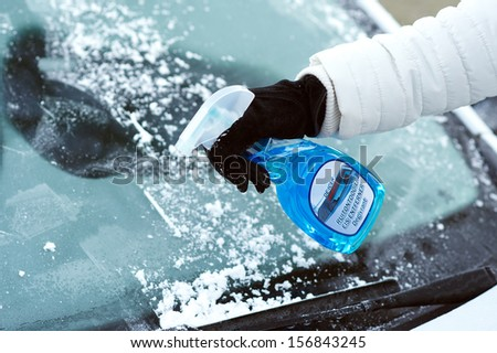 ice scraping en defrost spray on car windscreen - stock photo