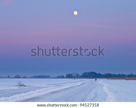 Ice skaters are making their way over a lake under the full moon - stock photo