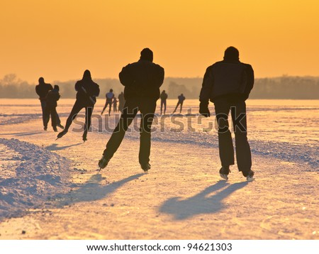 Ice skaters on a dutch lake seen on their back during the eleven cities tour - stock photo