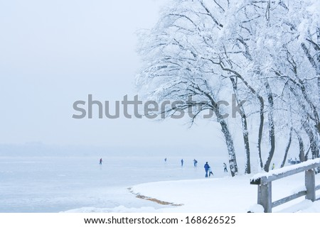 Ice Skaters on a Misty Frozen Alpine Lake - stock photo