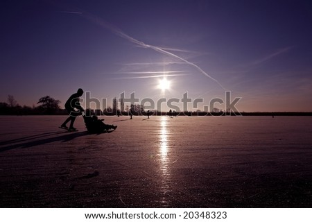 Ice skating and sledging in winter on a frozen lake in the Netherlands - stock photo
