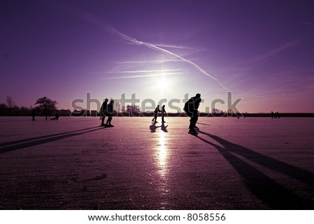 Ice skating at sunset in the Netherlands - stock photo