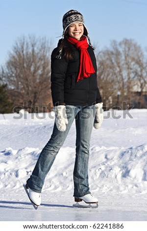 Ice skating girl. Young woman skating on ice with figure skates outdoors in the snow. Quebec,City, Canada. - stock photo