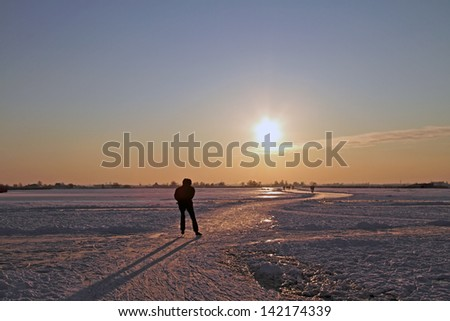 Ice skating in the countryside from the Netherlands at sunset - stock photo