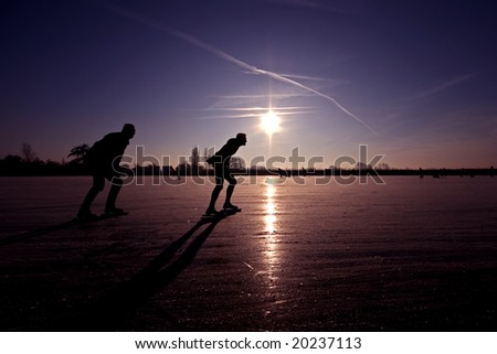 Ice skating in the Netherlands at a beautiful purple sunset - stock photo