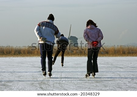Ice skating on a cold winterday in the countryside on a frozen lake  in the Netherlands - stock photo