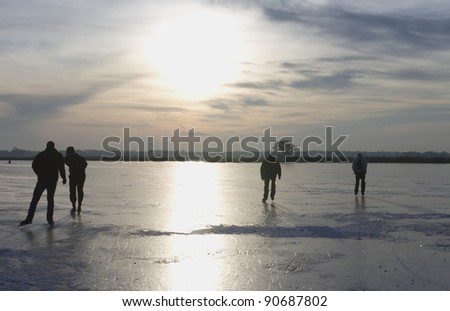 Ice skating on a frozen lake in the Netherlands - stock photo