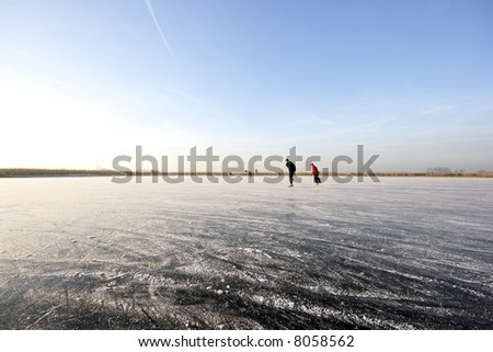 Ice skating on a wide open lake in the countryside in the Netherlands - stock photo