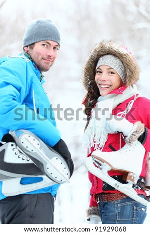 Ice skating winter couple smiling happy holding ice skates outdoors. Beautiful young couple, Asian woman, Caucasian man outside on snow winter day. - stock photo